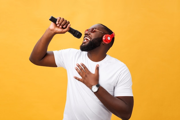 Jeune beau garçon afro-américain chantant émotionnel avec micro.