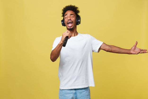 Jeune beau garçon afro-américain chanter l'opéra émotionnel avec microphone.
