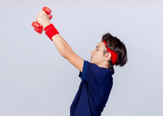Jeune beau garçon sportif portant un bandeau et des bracelets avec un appareil dentaire debout en vue de profil à la recherche d'haltères tout droit isolé sur fond blanc avec espace de copie