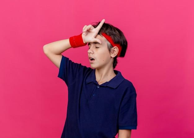 Jeune beau garçon sportif portant un bandeau et des bracelets avec un appareil dentaire faisant un geste perdant sur le front avec les yeux fermés isolé sur fond cramoisi avec espace de copie