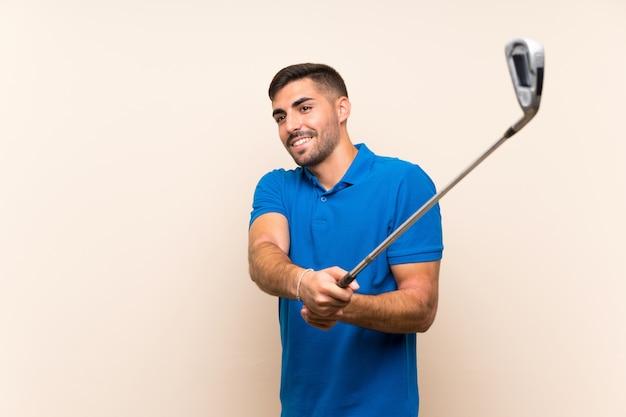 Jeune beau golfeur homme sur mur isolé