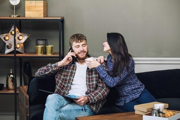 Jeune beau et heureux couple homme et femme à la maison avec tablette et mobile sur canapé