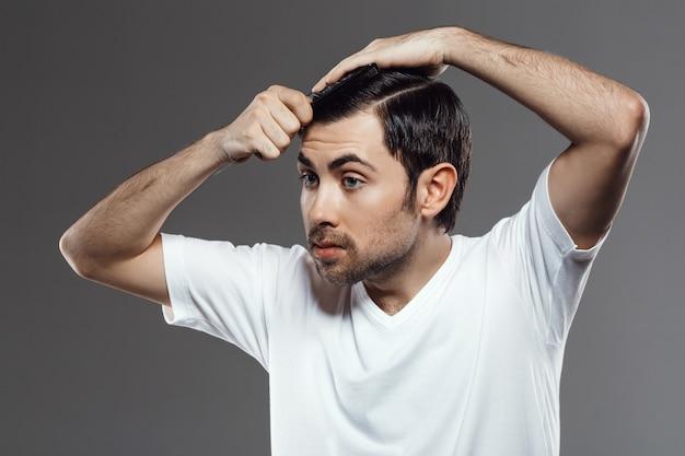 Jeune, beau, homme, peigner, cheveux, faire, coupe cheveux