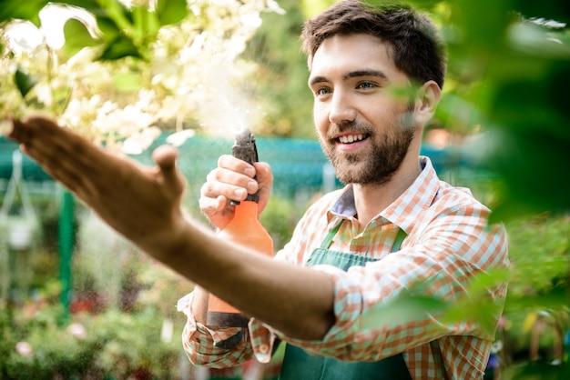 Jeune beau jardinier gai souriant, arrosant, en prenant soin des fleurs
