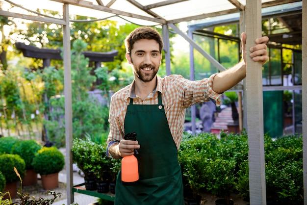 Jeune beau jardinier gai souriant, posant parmi les plantes et les fleurs