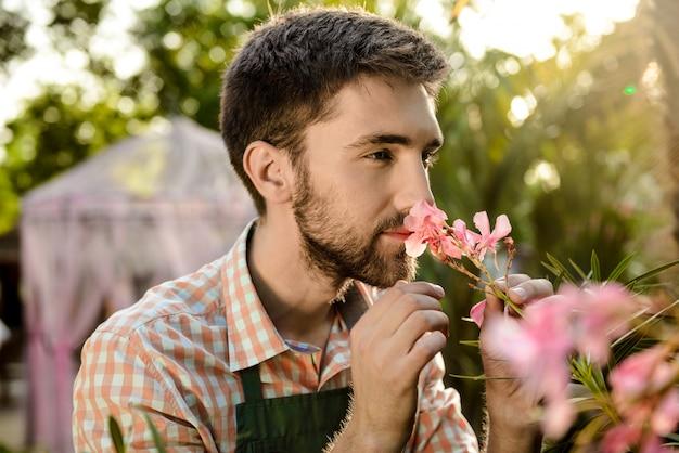 Jeune beau jardinier gai souriant, reniflant des fleurs roses