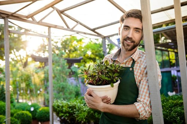 Jeune beau jardinier gai souriant, tenant le pot avec la plante