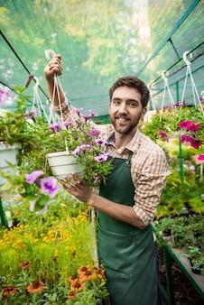 Jeune beau jardinier joyeux souriant, en prenant soin des fleurs