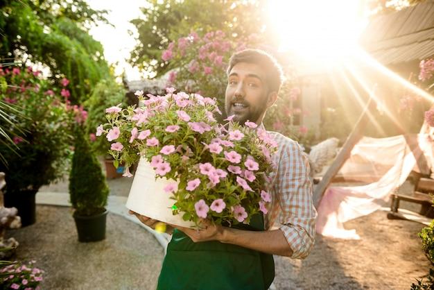Jeune beau jardinier souriant, tenant un gros pot avec des fleurs