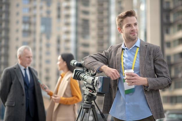 Jeune beau journaliste prenant un café se sentant bien pendant la pause de travail