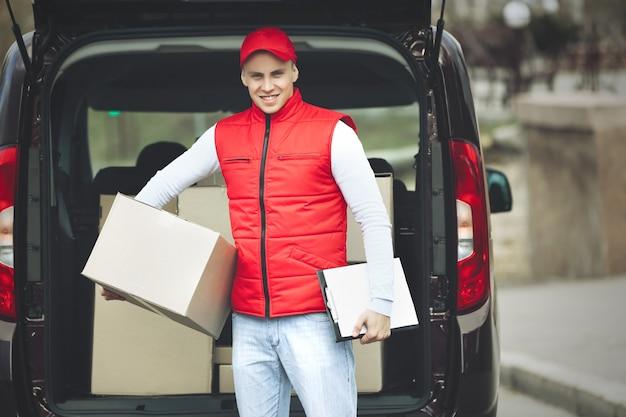 Jeune beau livreur debout près de la voiture avec des boîtes et des paquets, à l'extérieur