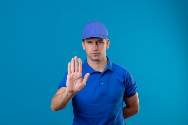 Jeune beau livreur en uniforme bleu et cap debout avec la main ouverte faisant panneau d'arrêt avec un geste de défense du visage fronçant sérieux sur le mur bleu