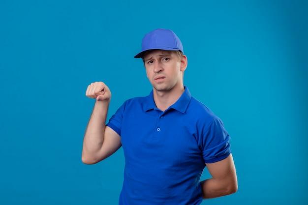 Jeune beau livreur en uniforme bleu et cap poing serrant montrant les biceps à la confiance debout sur le mur bleu