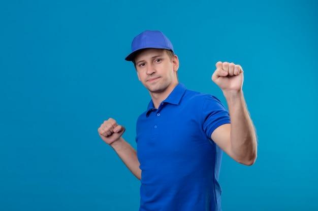 Jeune beau livreur en uniforme bleu et cap serrant les poings heureux et positif debout sur le mur bleu