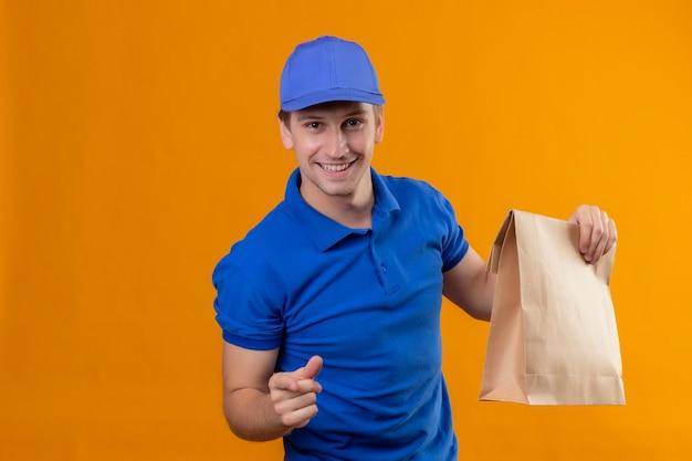 Jeune beau livreur en uniforme bleu et cap tenant le paquet de papier pointant avec le doigt à la caméra souriant sympathique positif et heureux debout sur le mur orange