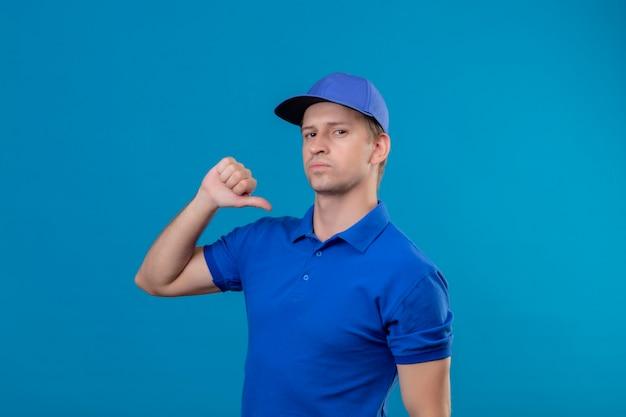 Jeune beau livreur en uniforme bleu et capuchon pointant vers lui-même avec le pouce à la confiance en soi et fier debout sur le mur bleu