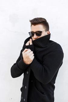 Jeune beau mec aux cheveux dans un pull noir et des lunettes de soleil debout près d'un mur blanc