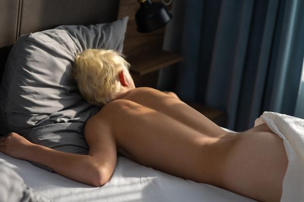 Jeune beau mec blond nu dans la chambre avec de grands rideaux de fenêtre et un lit