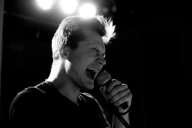 Jeune beau mec chante émotionnellement et parle dans le microphone. photographie noir et blanc