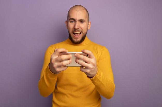 Jeune beau mec en colère jouant au téléphone