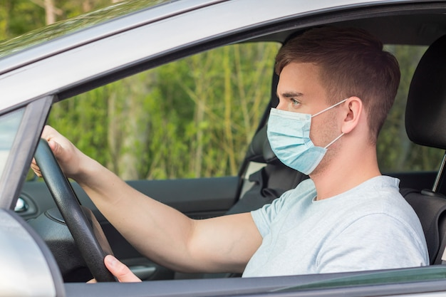 Jeune beau mec concentré, chauffeur, homme sérieux conduisant une voiture avec un masque de protection médical sur son visage, tenant une roue automobile, profitant d'un voyage sur la route. coronavirus, pandémie, virus covid-19 concept