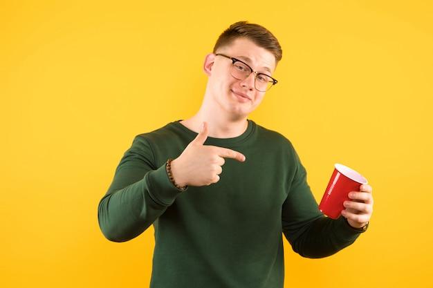 Jeune beau mec confiant en pull vert, tenant une tasse en plastique rouge