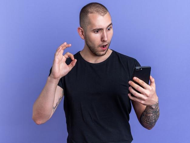 Jeune beau mec confus portant un t-shirt noir tenant et regardant le téléphone montrant un geste correct isolé sur un mur bleu