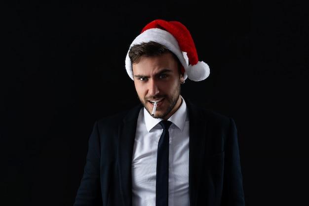 Jeune beau mec en costume d'affaires et bonnet de noel se dresse sur fond gris en studio avec visage sérieux et cigarette fumer portrait homme d'affaires avec bannière de vacances humeur de noël