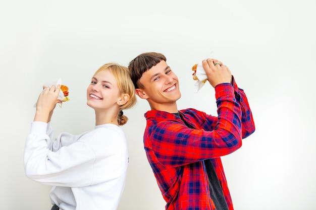 Jeune beau mec couple heureux et fille mangeant de gros hamburgers délicieux sur fond blanc