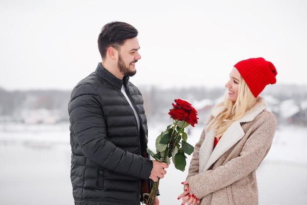 Jeune beau mec donnant à une femme un bouquet de roses le jour de la saint-valentin
