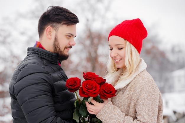 Jeune beau mec donnant à une fille un bouquet de roses le jour de la saint-valentin