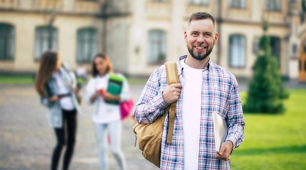 Jeune beau mec étudiant barbu dans des vêtements décontractés avec sac à dos et livres en mains marche et pose sur les bâtiments de l'université