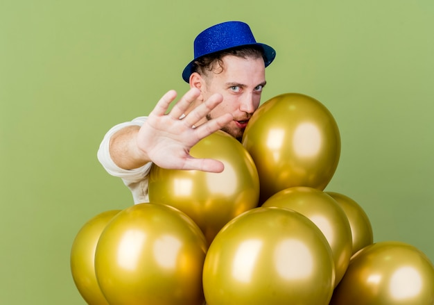 Jeune beau mec de fête slave portant chapeau de fête debout derrière des ballons regardant la caméra étirant la main vers la caméra faisant le geste d'arrêt isolé sur fond vert olive
