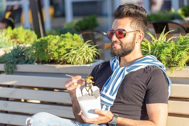 Jeune beau mec hipster mangeant des nouilles chinoises dans une boîte à lunch alors qu'il était assis dans un banc de parc