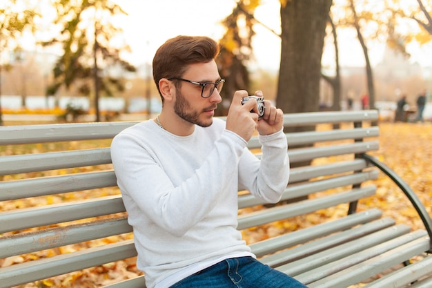 Jeune beau mec hipster se promène dans un magnifique parc d'automne