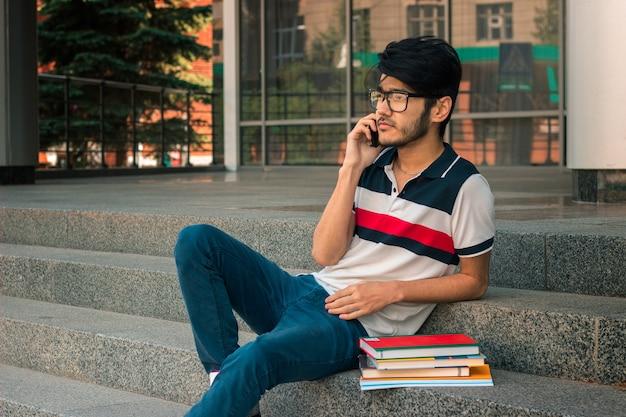 Jeune beau mec à lunettes et livres assis sur les escaliers et regarde au loin