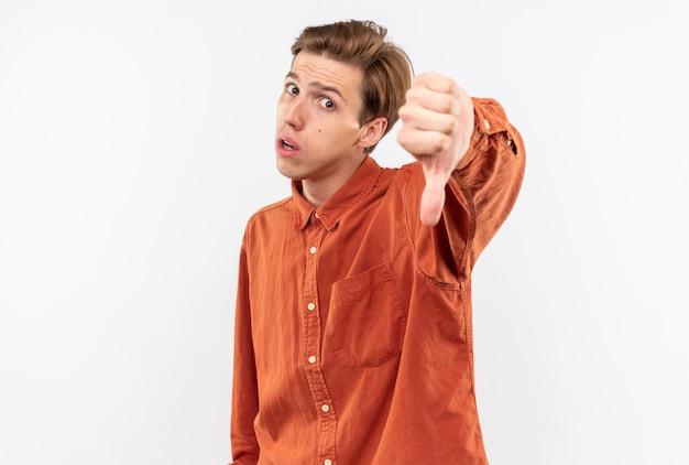 Jeune beau mec mécontent portant une chemise rouge montrant le pouce vers le bas