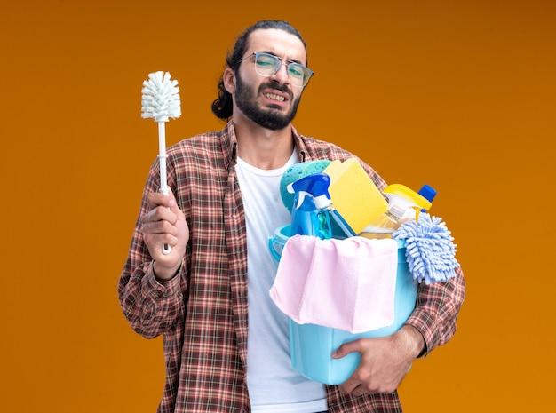 Jeune beau mec de nettoyage mécontent portant un t-shirt tenant un seau d'outils de nettoyage avec une brosse isolée sur un mur orange