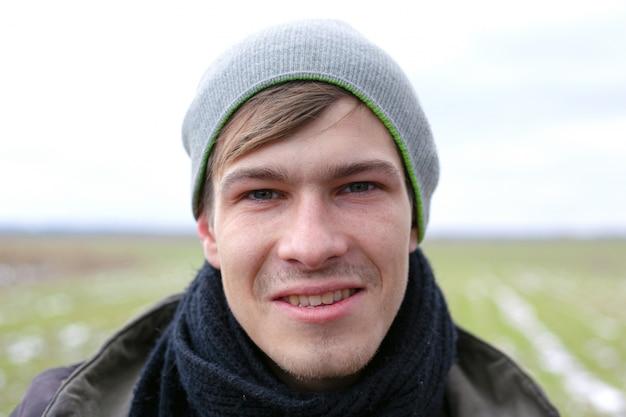 Jeune beau mec non rasé portrait de visage gros plan sur un fond de champ de printemps avec de l'herbe verte.