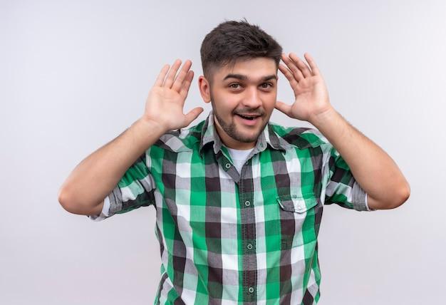 Jeune beau mec portant une chemise à carreaux essayant d'entendre debout sur un mur blanc