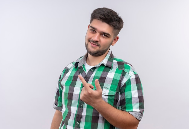 Jeune beau mec portant une chemise à carreaux montrant signe de baise avec le majeur debout sur un mur blanc