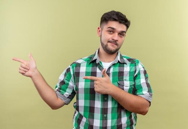 Jeune beau mec portant une chemise à carreaux pointant vers la droite avec l'index debout sur un mur kaki
