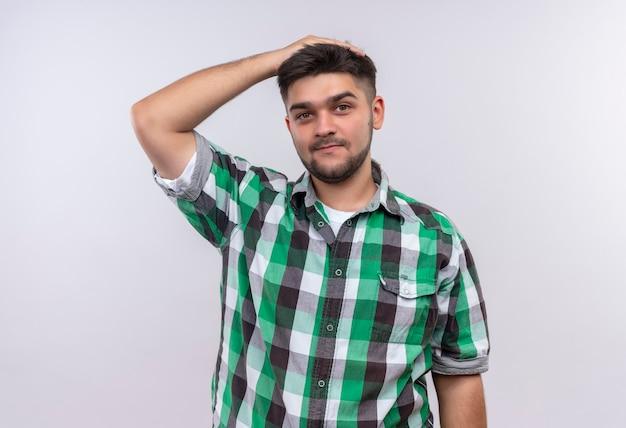 Jeune beau mec portant une chemise à carreaux redressant ses cheveux avec la main debout sur un mur blanc