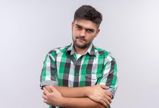 Jeune beau mec portant une chemise à carreaux à sérieusement debout sur un mur blanc