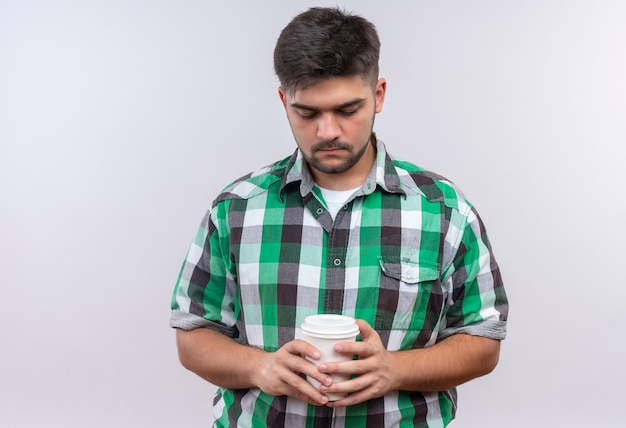Jeune beau mec portant une chemise à carreaux à tristement vers le bas sur sa tasse de café en plastique debout sur un mur blanc