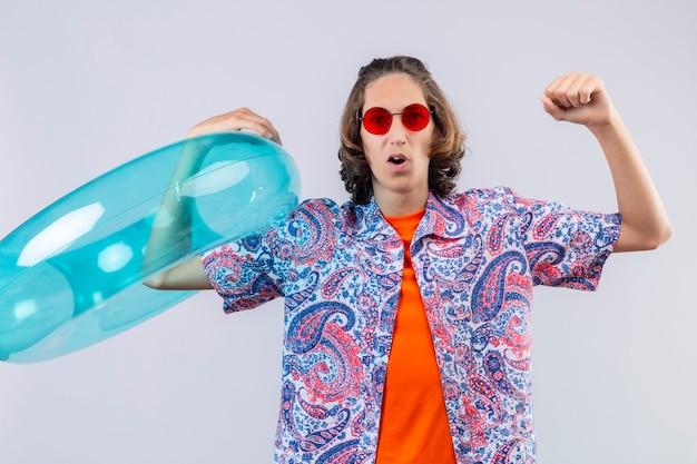 Jeune beau mec portant des lunettes de soleil rouges tenant un anneau gonflable levant le poing après une victoire sortie et heureux debout sur fond blanc