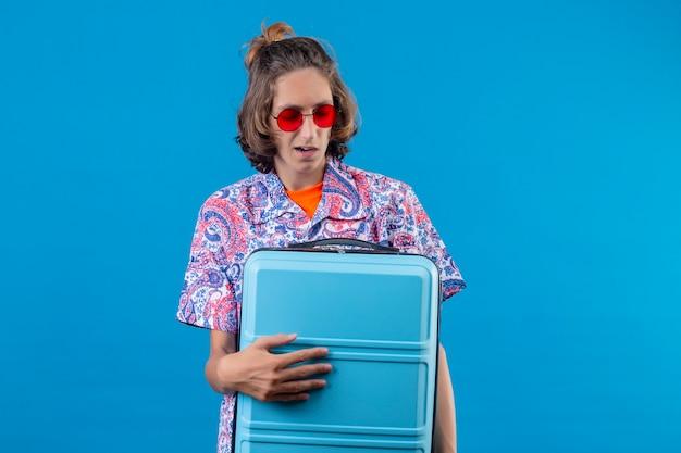 Jeune beau mec portant des lunettes de soleil rouges tenant une valise de voyage à la confusion debout sur fond bleu