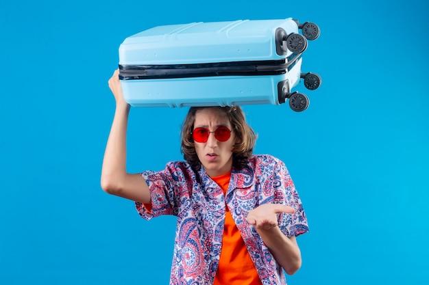 Jeune beau mec portant des lunettes de soleil rouges tenant une valise de voyage désemparé et confus n'ayant pas de réponse étalant les bras debout sur fond bleu
