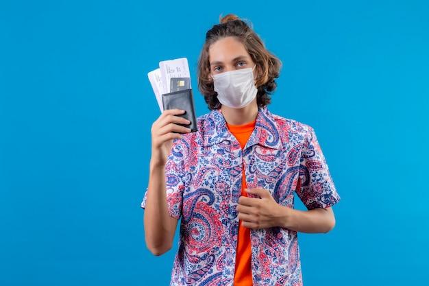 Jeune beau mec portant un masque de protection du visage tenant des billets d'avion à la recherche d'une expression confiante debout sur fond bleu