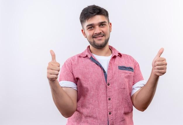 Jeune beau mec portant un polo rose faisant des pouces heureux debout sur un mur blanc